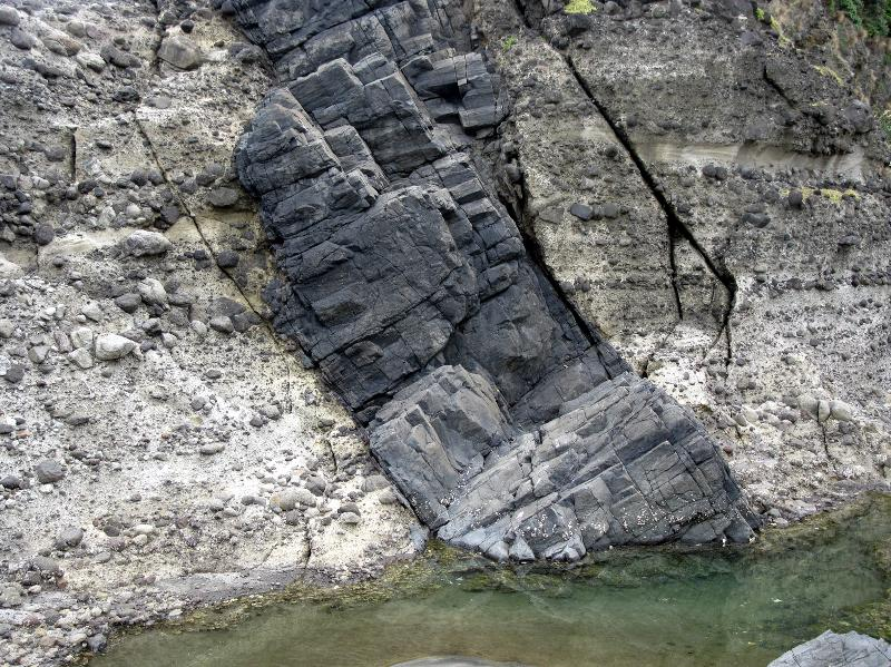Image #A dike of andesite intruding layered volcanic conglomerate outside the crater, Farley Pt.